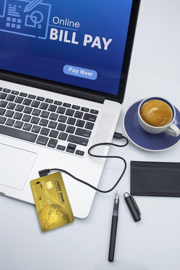 Cuentas que pagan en línea con un ordenador portátil foto de archivo