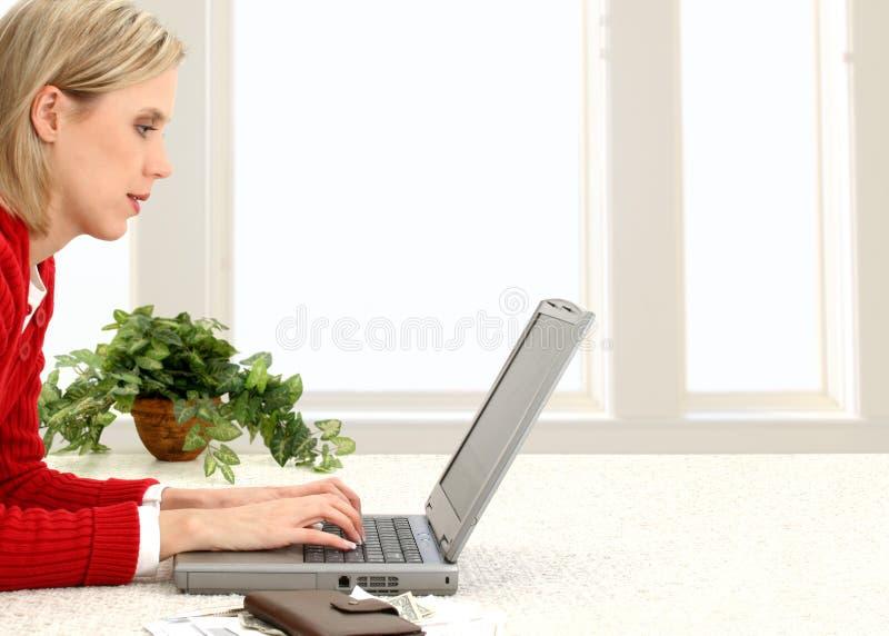 Cuentas que pagan hermosas de la mujer joven en línea fotografía de archivo libre de regalías