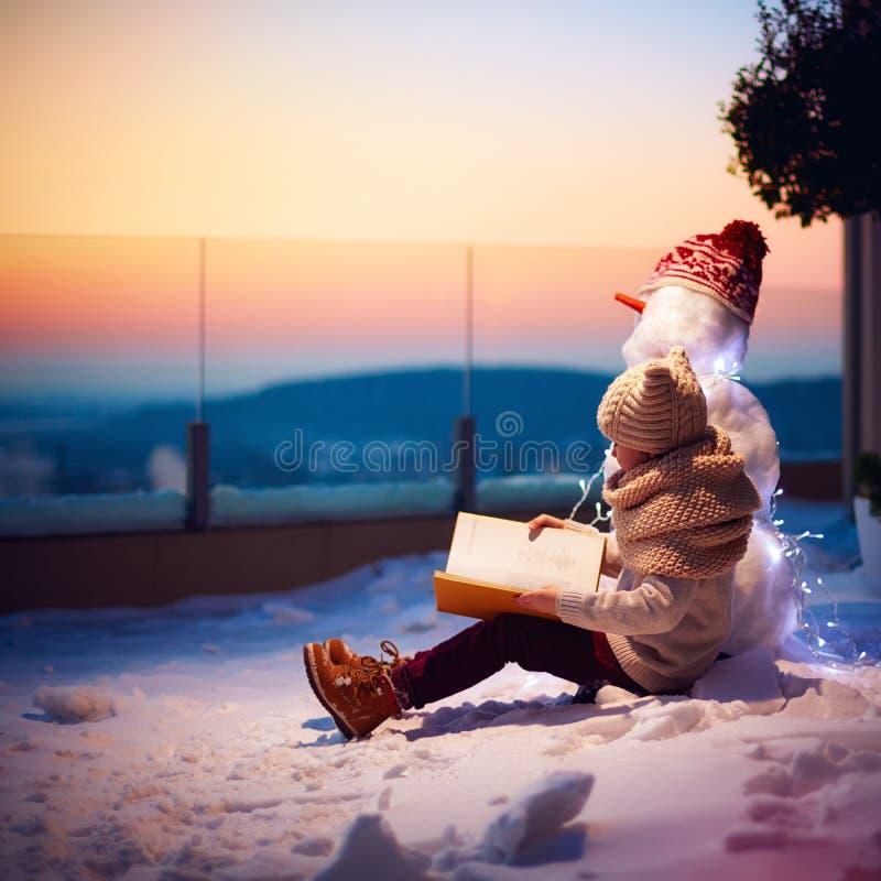 Cuento de hadas del invierno muchacho joven, niño que lee el libro interesante a su muñeco de nieve del amigo en el patio trasero fotografía de archivo libre de regalías