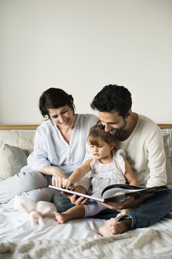 Cuentos de hadas de lectura de la familia caucásica ellos hija con felicidad fotos de archivo
