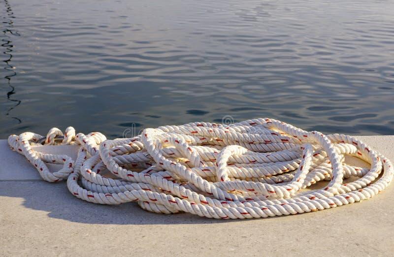 Cuerda blanca en el muelle de piedra por el mar para amarrar los barcos o los yates foto de archivo