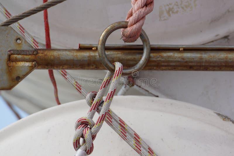 Cuerda de acero y gancho oxidado en el lado trasero del barco de navegación Bandera de Grecia y del castillo histórico en el fo imágenes de archivo libres de regalías