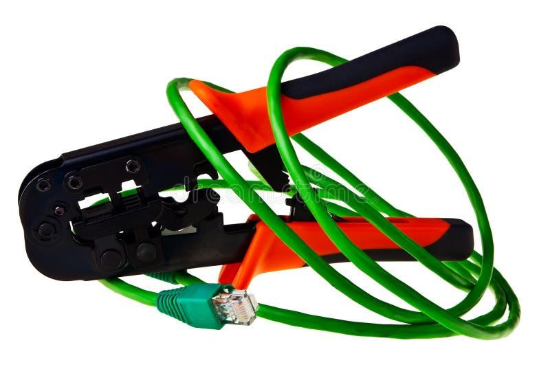 Cuerda de corrección verde con la herramienta del arrugador RJ45. imagenes de archivo