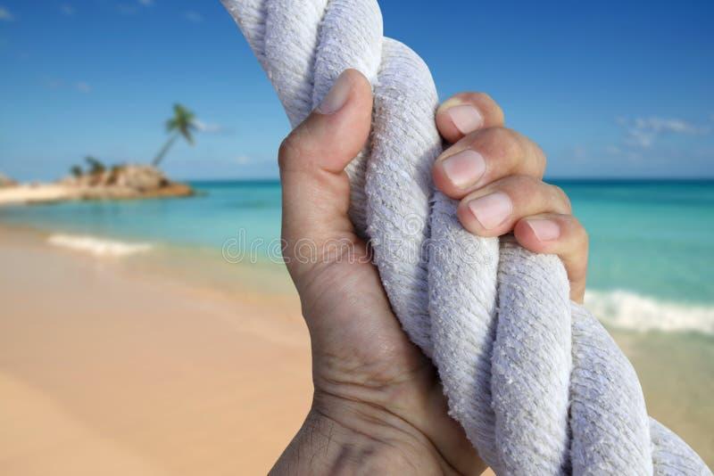 Cuerda de la playa del paraíso de la aventura del apretón del gancho agarrador de la mano del hombre fotografía de archivo