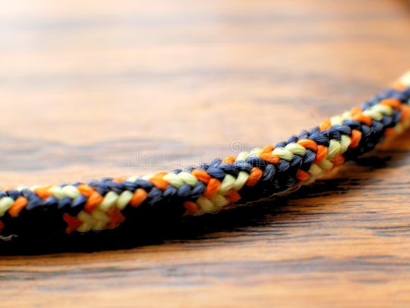 Cuerda de nylon trenzada en el fondo de madera del grano para subir, acampando imagen de archivo libre de regalías