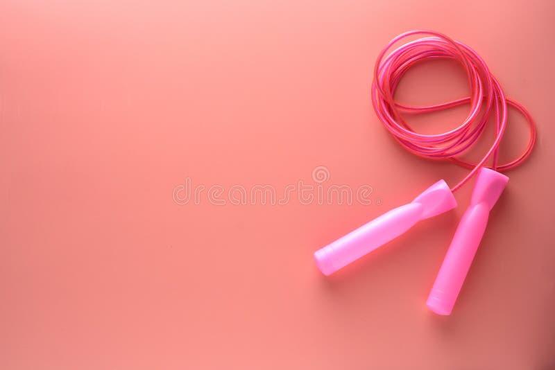 Cuerda de salto rosada o cuerda que salta aislada en fondo rosado Deportes, aptitud, concepto cardiio, sano del entrenamiento imagenes de archivo