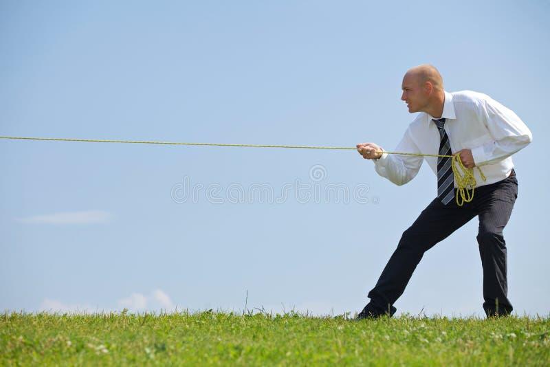 Cuerda de tracción del hombre de negocios en parque foto de archivo