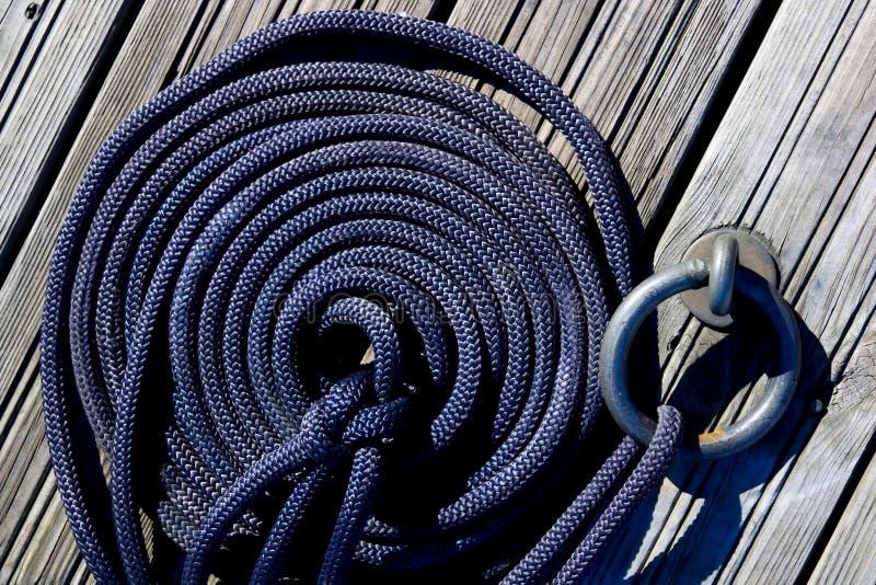 Cuerda náutica del amarre en el embarcadero de madera fotografía de archivo