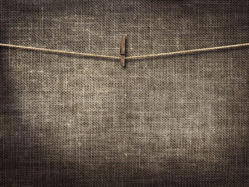 Cuerda para tender la ropa con las pinzas en el fondo de lino foto de archivo