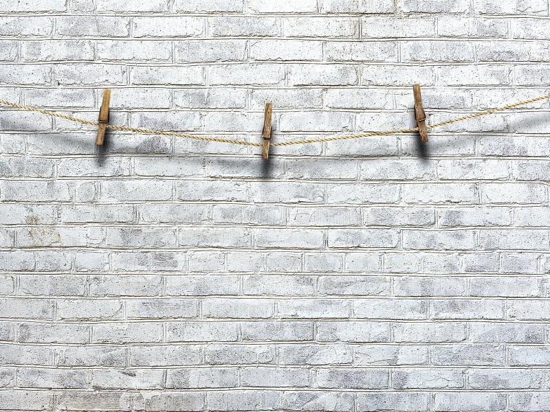 Cuerda para tender la ropa con las pinzas en un fondo de una pared de ladrillo imagen de archivo libre de regalías