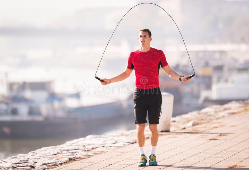 Cuerda que salta de la ropa de deportes del hombre que lleva joven en el muelle durante otoño fotografía de archivo libre de regalías