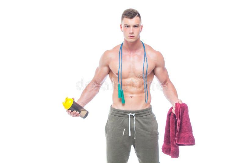 Cuerda que salta del hombre muscular Retrato del hombre joven muscular con el agua potable de la cuerda de salto con la toalla ro imágenes de archivo libres de regalías