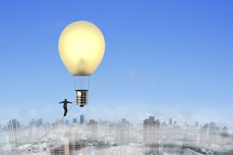 Cuerda tirante que camina del hombre de negocios hacia el bal del aire caliente de la forma de la bombilla fotografía de archivo