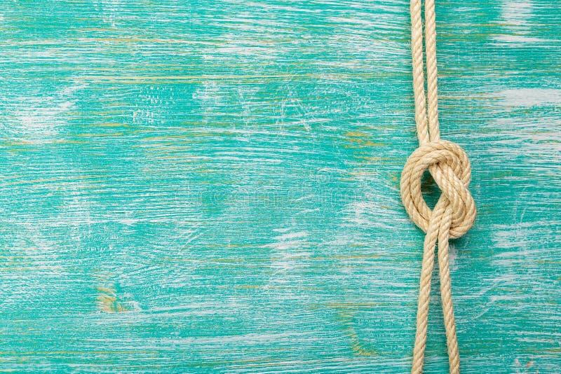 Cuerdas atadas con los nudos en fondo de la turquesa fotos de archivo