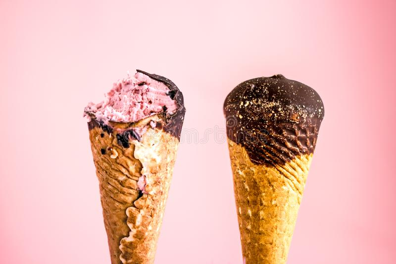 Cuernos del helado de chocolate Helado en un cono de la galleta en el esmalte del chocolate, arrancado con los dientes y un cono  imagen de archivo