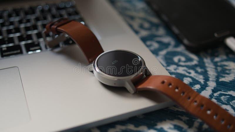 Cuero elegante del reloj en el ordenador portátil en smartphone del escritorio fotos de archivo