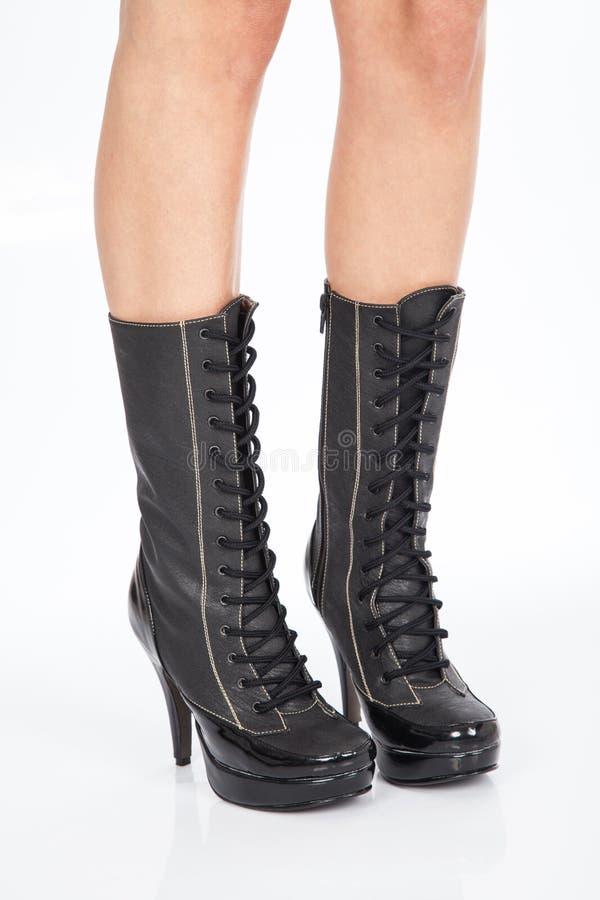Cuero negro de las botas para las mujeres en las calzadas blancas del fondo imagenes de archivo
