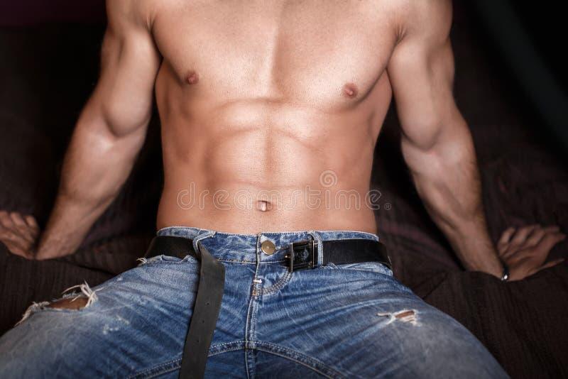 Cuerpo atractivo del hombre con seis paquetes que se sientan en cama foto de archivo libre de regalías