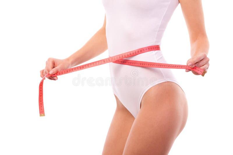 Cuerpo de la mujer con la cinta de la medida Ciérrese para arriba de cuerpo femenino deportivo y hermoso Cintura de medición bron foto de archivo libre de regalías