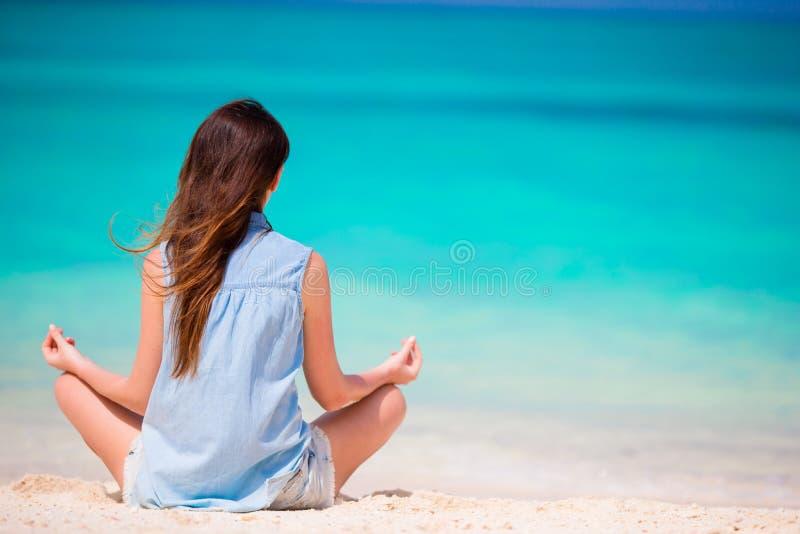 Cuerpo de la mujer hermosa en una meditación en la playa imagen de archivo libre de regalías