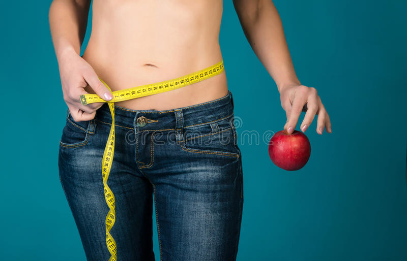 Cuerpo femenino apto con la manzana y la cinta métrica Aptitud sana y consumición, concepto de la forma de vida de la dieta fotografía de archivo libre de regalías