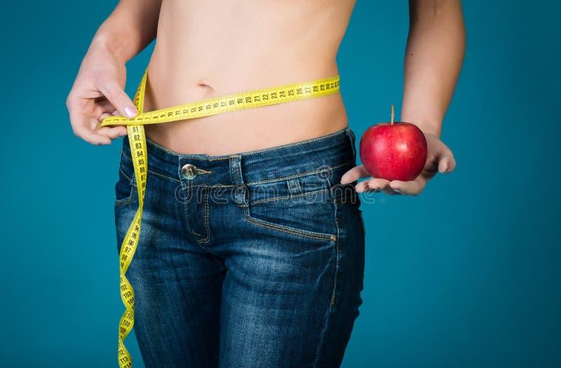 Cuerpo femenino apto con la manzana y la cinta métrica en fondo azul Aptitud sana y consumición de concepto de la forma de vida imagen de archivo