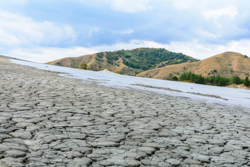 Cuesta agrietada con el volcán del fango y el cielo nublado Tierra seca en natur imagen de archivo