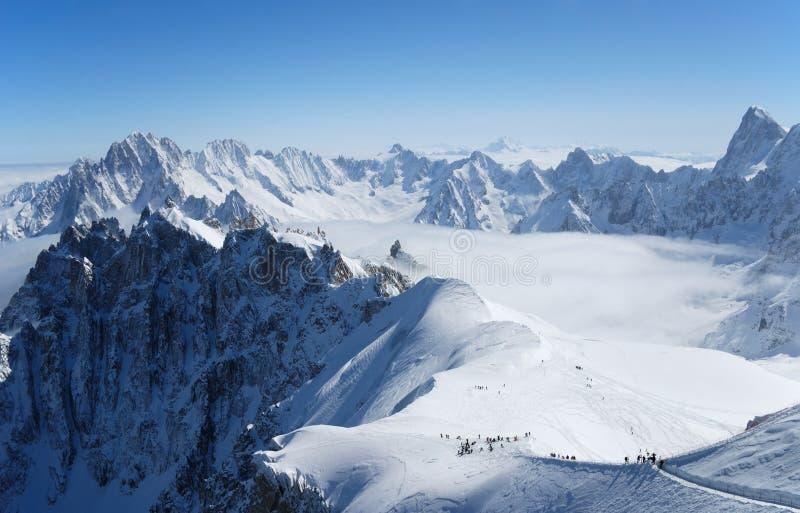 Cuesta de la nieve con los montaña-esquiadores, las montan@as fotos de archivo