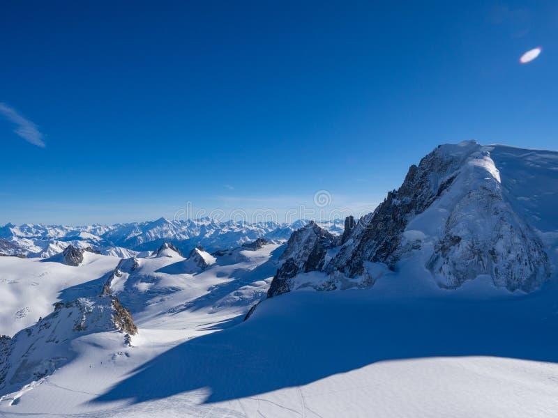 Cuesta de la nieve con la montaña contra el cielo azul y los picos escarpados de las montañas, Mont Blanc, Francia foto de archivo