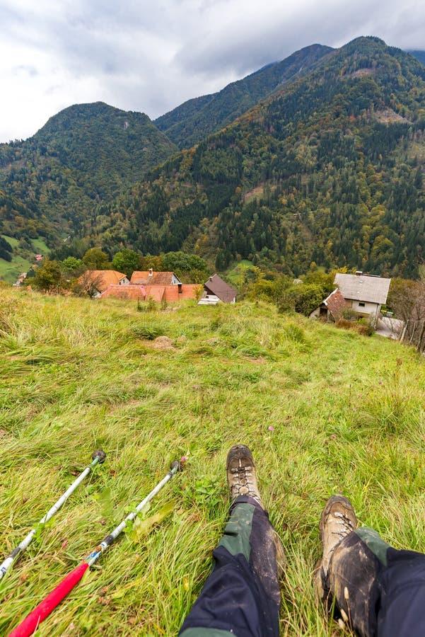 Cuesta de montaña de reclinación del Backpacker, opinión del pueblo del bosque foto de archivo libre de regalías