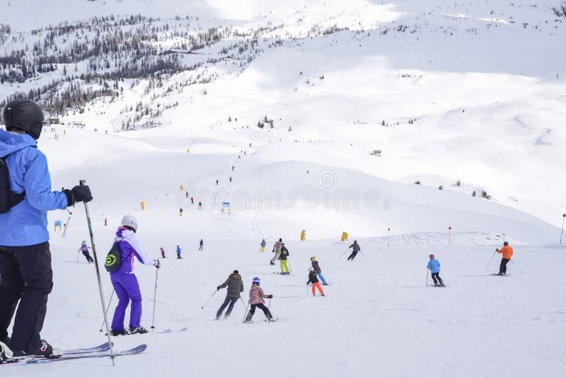 Cuesta del esquí con los esquiadores en las montañas imagenes de archivo
