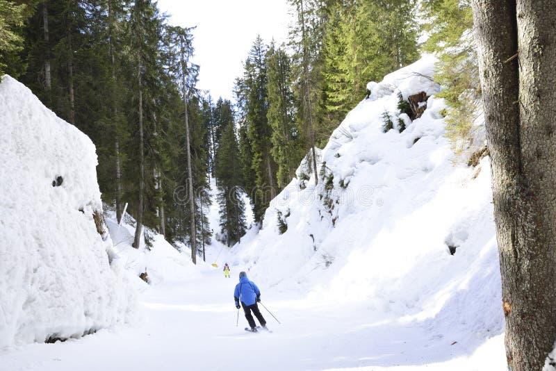 Cuesta del esquí con los esquiadores en las montañas imagen de archivo