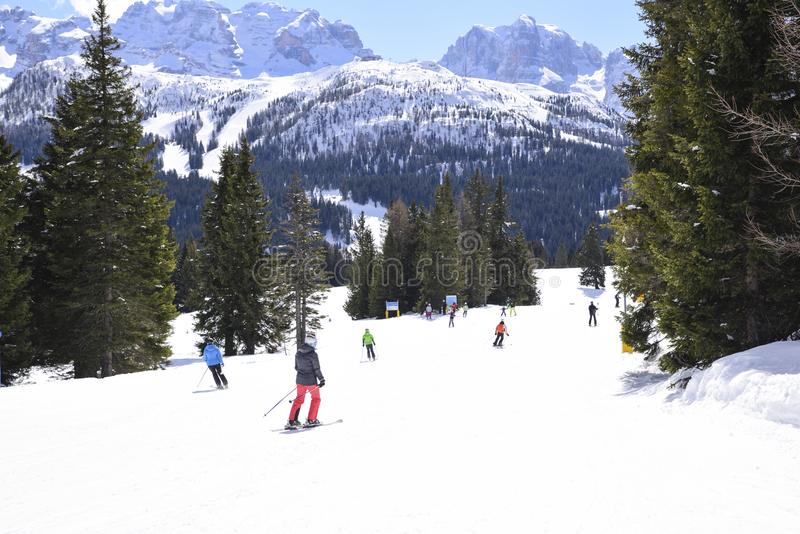 Cuesta del esquí con los esquiadores en las montañas imagen de archivo libre de regalías