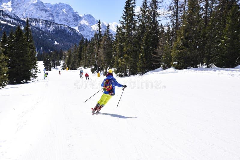 Cuesta del esquí con los esquiadores en las montañas fotos de archivo