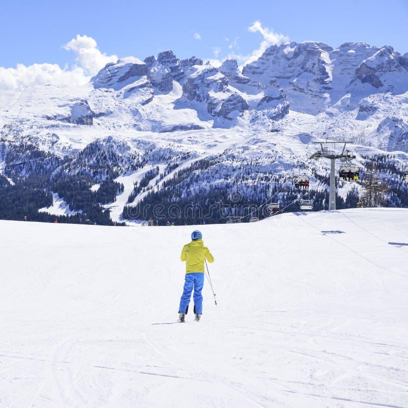 Cuesta del esquí con los esquiadores en las montañas fotografía de archivo libre de regalías