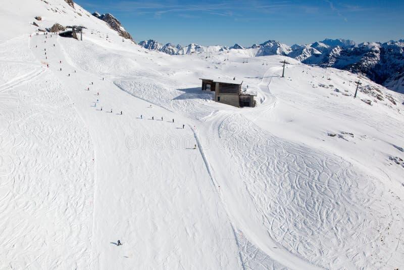 Cuesta del esquí con los esquiadores en las montañas foto de archivo