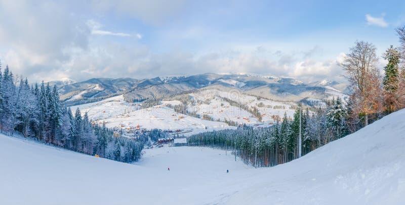Cuesta del esquí contra de cordillera y pueblo en Cárpatos imagen de archivo libre de regalías
