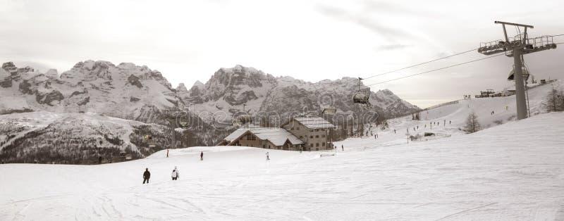 Cuestas del esquí con los esquiadores en la puesta del sol imágenes de archivo libres de regalías