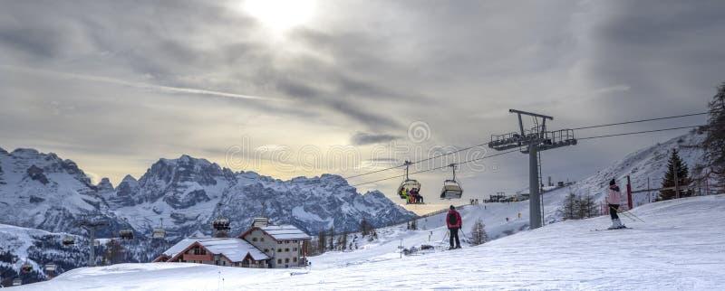 Cuestas del esquí con los esquiadores en la puesta del sol fotos de archivo