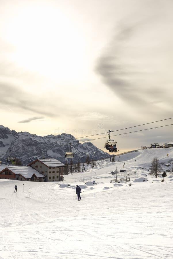 Cuestas del esquí con los esquiadores en la puesta del sol Trentino, Italia foto de archivo