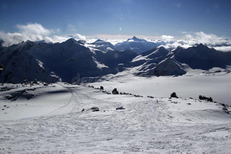 Cuestas fuera de pista de las altas montañas para el freeride con los rastros de esquís y de snowboard, día de invierno soleado,  foto de archivo