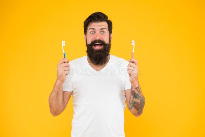 Cuestiones de boca Hombre con barba sonrisa feliz con cepillos de dientes Feliz hipster sostener el fondo amarillo Higiene dental imagen de archivo