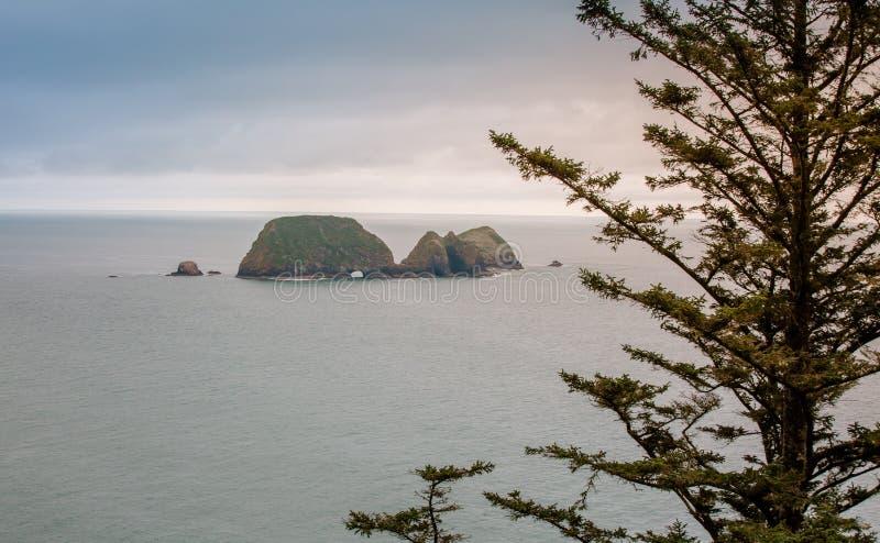 Cueva grande de la isla de la roca en el océano del Océano Pacífico foto de archivo