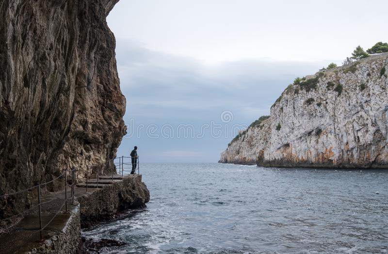 Cuevas de Zinzulusa, cerca de Castro en la península de Salento en Puglia, Italia La persona se coloca en tablón de cuadrilla en  fotos de archivo libres de regalías