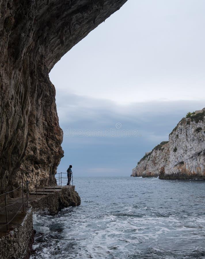 Cuevas de Zinzulusa, cerca de Castro en la península de Salento en Puglia, Italia Persona en soportes de la silueta en el tablón  imagenes de archivo