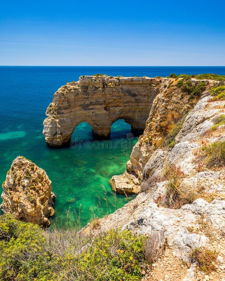 Cuevas naturales en la playa de Marinha, Algarve Portugal Arcos del acantilado de la roca en la agua de mar de la playa y de la t fotos de archivo libres de regalías
