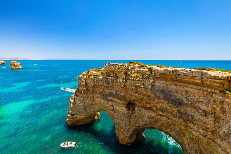 Cuevas naturales en la playa de Marinha, Algarve Portugal Arcos del acantilado de la roca en la agua de mar de la playa y de la t foto de archivo