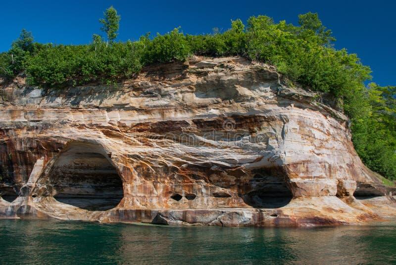 Cuevas no profundas en los acantilados del lago Superior, rocas representadas N foto de archivo
