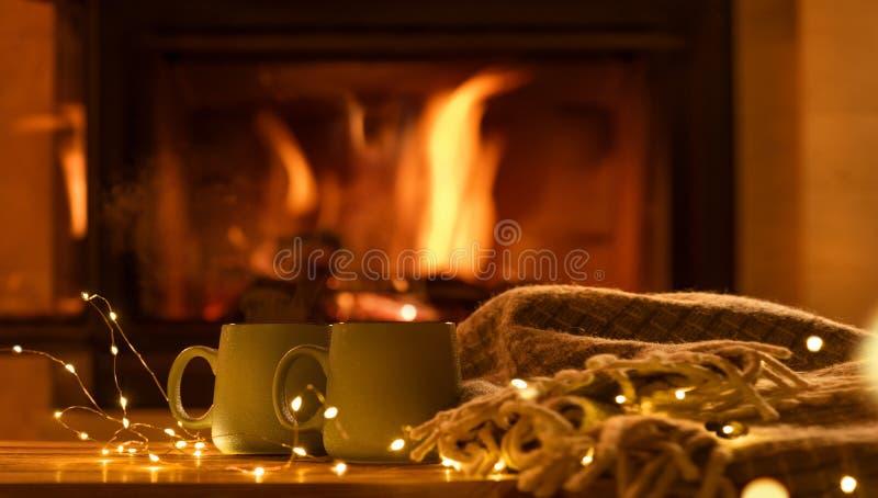 Cueza al vapor de tazas con un cacao caliente en el fondo de la chimenea imagen de archivo