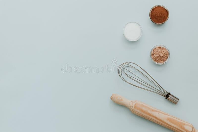 Cueza el sistema de herramientas con los ingredientes en el fondo en colores pastel, visión superior fotografía de archivo